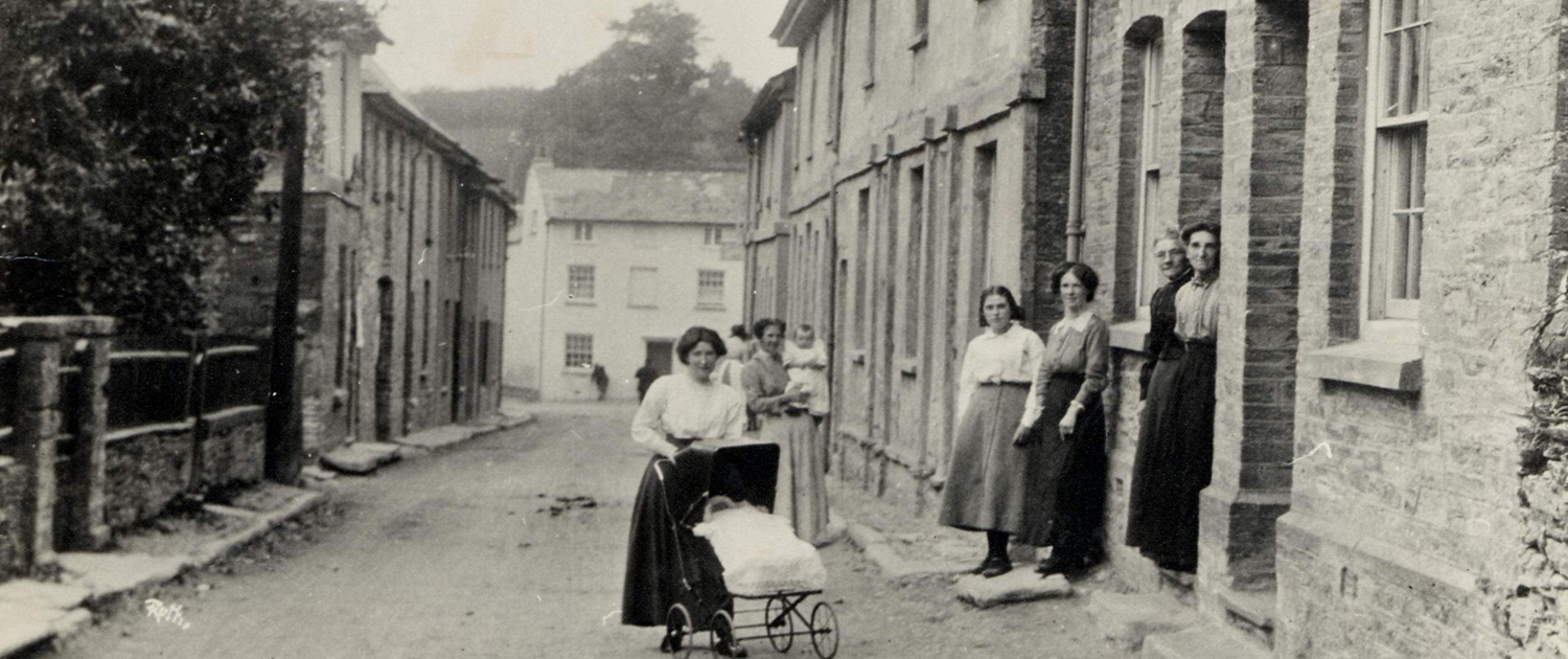 Group of women and children in the main street of Aveton Gifford, c. 1900