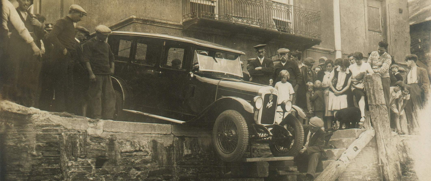 Vintage car balanced over quay edge, crowd of onlookers watching attempts to salvage it