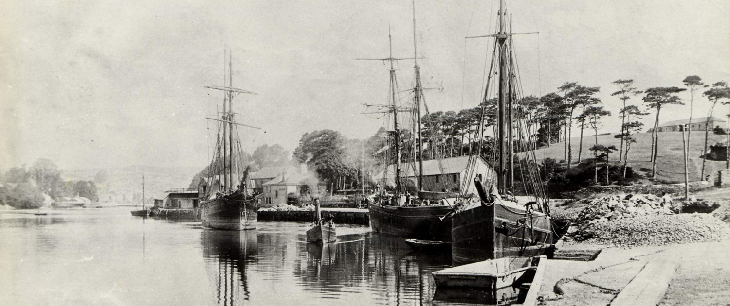 Bonds Quay on the Kingsbridge Estuary c. 1900, three sailing vessels moored and small steam launch passing