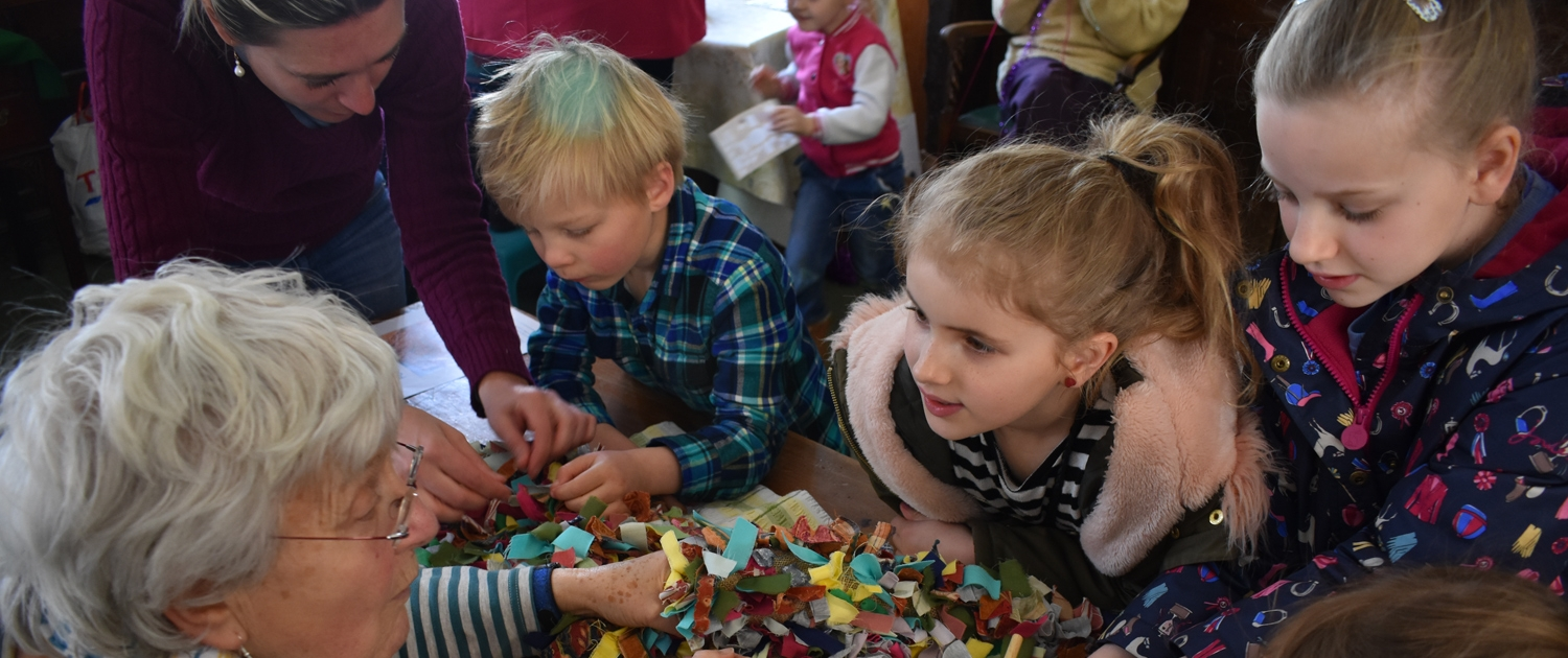 Museum volunteer and children working on a rag rug during Family Day