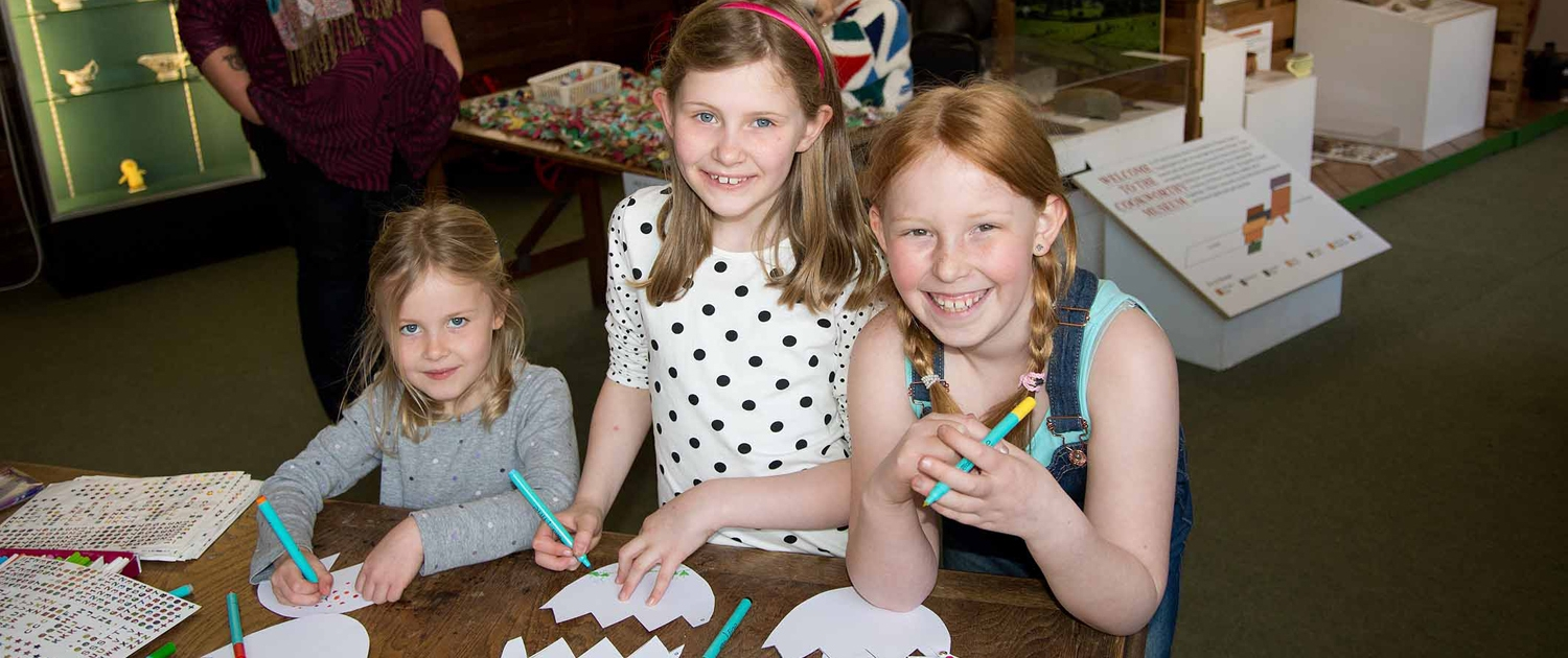 Three children enjoying drawing activities during a museum Family Day