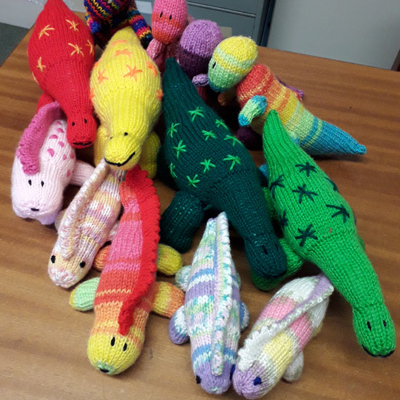 Multicoloured knitted dinosaurs on sale in the museum
